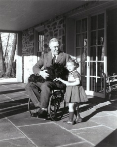 President Roosevelt in his wheelchair on the porch at Top Cottage in Hyde Park, NY with Ruthie Bie and Fala. February 1941.