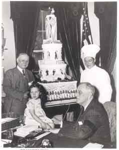FDR pictured receiving a birthday cake decorated with checks for the National Foundation for Infantile Paralysis. January, 1942